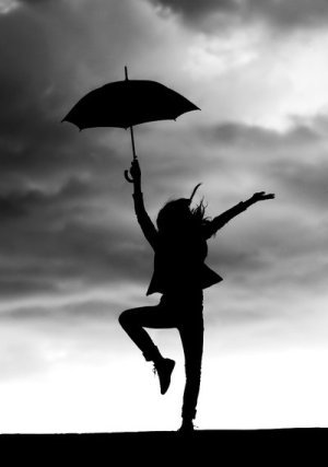 Woman holding umbrella and dancing with storm clouds above